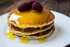 Stack of pancakes with honey and raspberry on white plate Stock Photography