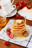 Stack of pancakes with honey syrup, butter and strawberry in a white plate Royalty Free Stock Photos