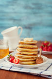 Stack of pancakes with honey syrup, butter and strawberry in a white plate Royalty Free Stock Photography