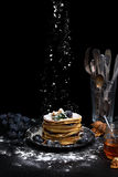 A stack of pancakes. Low key image.  There is a stack of pancakes on a dark table, near there is bunch grapes, a jar of honey and a some nuts Stock Image