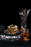 A stack of pancakes. Low key image.  There is a stack of pancakes on a dark table, near there is bunch grapes, a jar of honey and a some nuts Stock Photo