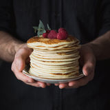 Stack of pancakes in man hands. Stack of pancakes with raspberries in male hands, closeup view, selective focus. Square crop Stock Image
