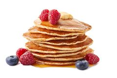 Stack of pancakes with maple syrup and fresh berries on white stock image