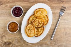 Stack of pancakes in oval dish, fork, bowls with jam Stock Images