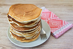 A stack of pancakes on a plate. On a wooden table Royalty Free Stock Photos