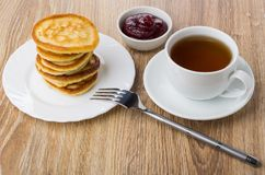Stack of pancakes in plate, fork, bowl with raspberry jam Stock Photos