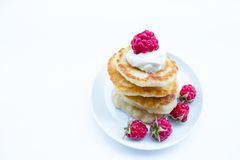Stack of pancakes on plate with raspberries and sour cream Royalty Free Stock Image
