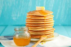 Stack of pancake with honey and butter on light-blue background. Stack of pancakes with pouring honey and piece of butter on plate with wooden spoon and jar with Stock Photography