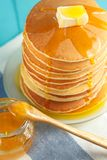 Close up of stack of pancake with honey and butter. Stack of pancakes with pouring honey on plate with wooden spoon and jar with honey. Concept of shrovetide Royalty Free Stock Photography