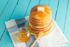 Close up of stack of pancake with honey and butter. Stack of pancakes with pouring honey on plate with wooden spoon and jar with honey. Concept of tasty Stock Image