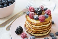 Stack of pancakes with raspberry, blackberry ,blueberry on white wooden background, side view. Close-up Royalty Free Stock Photo