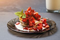Stack of pancakes with ripe strawberries and pouring by jogurt. Stack of hot pancakes with ripe strawberries and pouring by jogurt royalty free stock photos