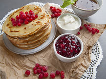 Stack of pancakes served with fresh cranberries, jam and cream. Stock Images