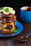 Stack of pancakes in the streaked chocolate with a banana on a d Stock Image