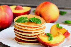 Stack of pancakes with syrup and grilled nectarines on a white plate. Easy sweet pancake recipe. Yummy breakfast or brunch. Sweet pancakes. Sweet pancakes. Fried Stock Photo