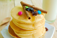 Stack of pancakes and syrup in plate on wooden table Royalty Free Stock Photos
