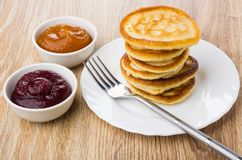 Stack of pancakes in white plate, fork, bowls with jam Royalty Free Stock Image