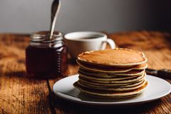 Stack of pancakes on white plate. Over wooden surface royalty free stock images
