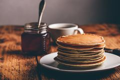 Stack of pancakes on white plate. Over wooden surface royalty free stock photo