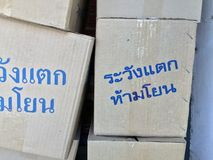 "Stack of paper box, grey color and blue color of text in Thai language ""Warning! Fragile, do not throw"". Pile up of gray box and metal Staples stock images"