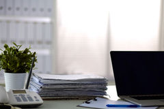 A stack of papers on the desk with a computer Royalty Free Stock Images