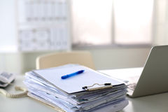 A stack of papers on the desk with a computer Royalty Free Stock Image
