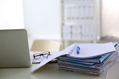 A stack of papers on the desk with a computer Royalty Free Stock Photos