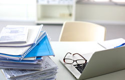 A stack of papers on the desk with a computer Royalty Free Stock Photography