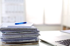 A stack of papers on the desk with a computer Stock Photos