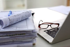 Stack of papers and glasses lying on table stock image