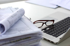 Stack of papers and glasses lying on table Royalty Free Stock Photo