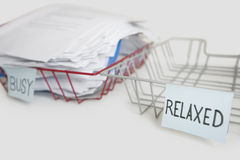 Stack of paperwork in busy tray with empty relaxed platter over white background Royalty Free Stock Photos