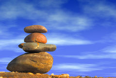 Stack of pebbles against blue Stock Images