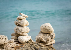 Stack of pebbles by ocean seaside Royalty Free Stock Photos