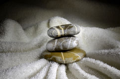 Stack of pebbles on towel Stock Photo