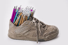 Stack of pens inserted to old  wear out sneaker Royalty Free Stock Images