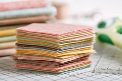 Stack of pentagon pieces of fabrics on white craft mat royalty free stock photography