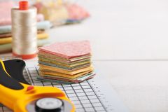 Stack of pentagon pieces of fabrics on white craft mat, sewing accessories stock photo