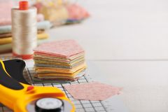Stack of pentagon pieces of fabrics on white craft mat, sewing accessories royalty free stock image