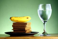 Stack or pile of crackers, a banana and a goblet of water Stock Photography