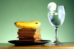 Stack or pile of crackers, a banana and a goblet of water with cucumber slices Royalty Free Stock Image