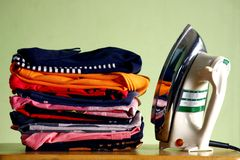 Stack or pile of folded shirts and an iron Stock Image