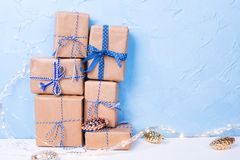 Stack or pile of wrapped boxes with presents, decorative golden cones and fairy lights on white textured background against blue stock images