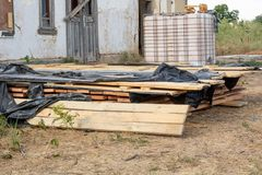 A stack of pine boards soaked in an antiseptic solution is dried at the construction site. Building materials for the construction of a frame house royalty free stock image