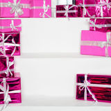 Stack of pink celebration gift boxes with ribbon bows on white table, free space for text. Winter holidays concept. Stack of pink celebration gift boxes with Royalty Free Stock Photography