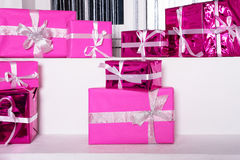 Stack of pink celebration gift boxes with ribbon bows on white table. Winter holidays concept. Royalty Free Stock Image