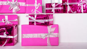 Stack of pink celebration gift boxes with ribbon bows on white table. Winter holidays concept. Stock Photo