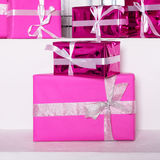 Stack of pink celebration gift boxes with ribbon bows on white table. Winter holidays concept. Stock Photography