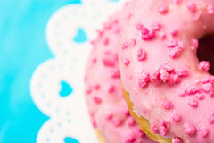 Stack of pink glazed doughnuts with sugar sprinkles on white cake stand with hearts, light blue background, copyspace, birthday, c Stock Image