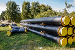Stack of pipes. A bunch of black and yellow construction pipes layed on the ground stock photo